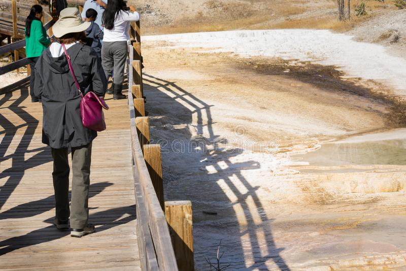 Touristen, die Landschaft entlang Gehweg bei Mammoth Hot Springs, Yellowstone Nationalpark genießen lizenzfreie stockfotografie