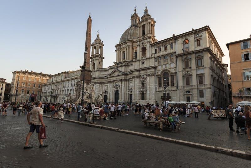 Touristen, die in Marktplatz Navona nah an dem Brunnen der vier Flüsse mit einem ägyptischen Obelisken und einem Sant Agnese Chur stockfotos