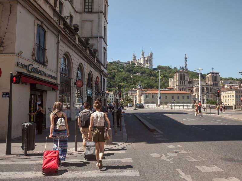 Touristen, die mit ihrem Gepäck und Koffern im Stadtzentrum von Lyon, mit dem ikonenhaften Markstein von Notre Dame de Fourviere  lizenzfreies stockfoto