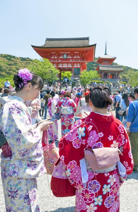 Touristen, die oben im traditionellen Kimono an Kiyomizu-deratempel, berühmter buddhistischer Tempel in Kyoto, Japan ankleiden lizenzfreie stockfotos