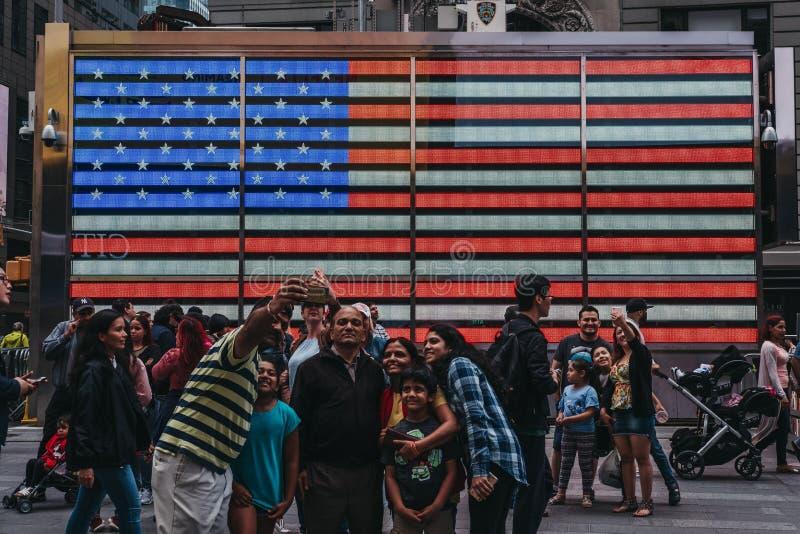 Touristen, die selfies herein von auf einer großen geführten amerikanischen Flagge im Ti nehmen stockfotos
