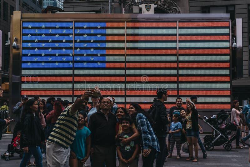 Touristen, die selfies herein von auf einer großen geführten amerikanischen Flagge im Ti nehmen stockbilder