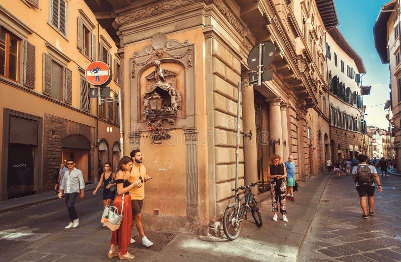 Touristen, die unter historische Entlastungen von schmalen Straßenhäusern alter Toskana-Stadt gehen stockbild