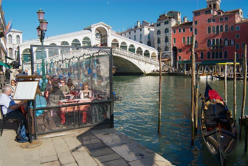 Touristen essen an der Caféterrasse angesichts der Brücke Markstein Ponte di Rialto über Grand Canal in Venedig, Italien zu Mitta lizenzfreies stockfoto