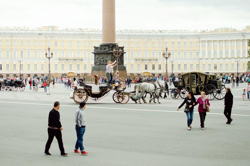 Touristen fahren in eine Pferdekutsche auf Palast-Quadrat in St Petersburg stockbilder
