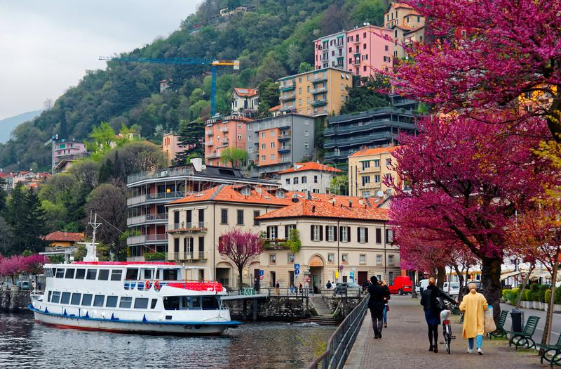 Touristen gehen auf eine Seeuferpromenade unter schöne blühende Bäume durch See Como in Lombardei Italien stockfotografie
