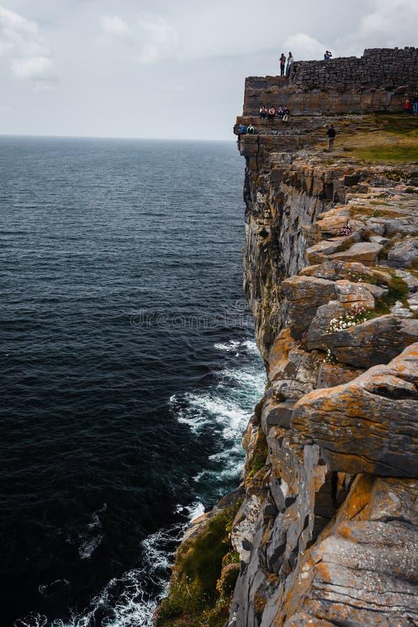 Touristen gehen entlang Rand der Klippen auf Inishmore Insel lizenzfreie stockfotografie