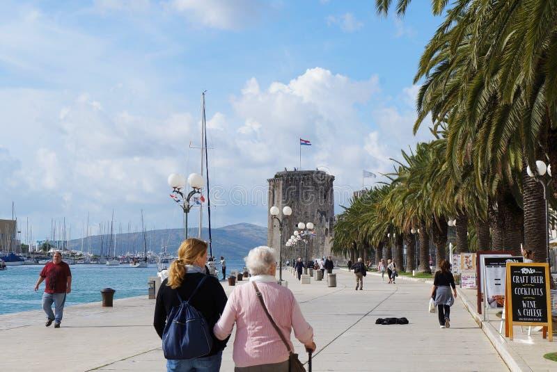 Touristen geht auf Seepromenade der alten Stadt Trogir lizenzfreies stockbild