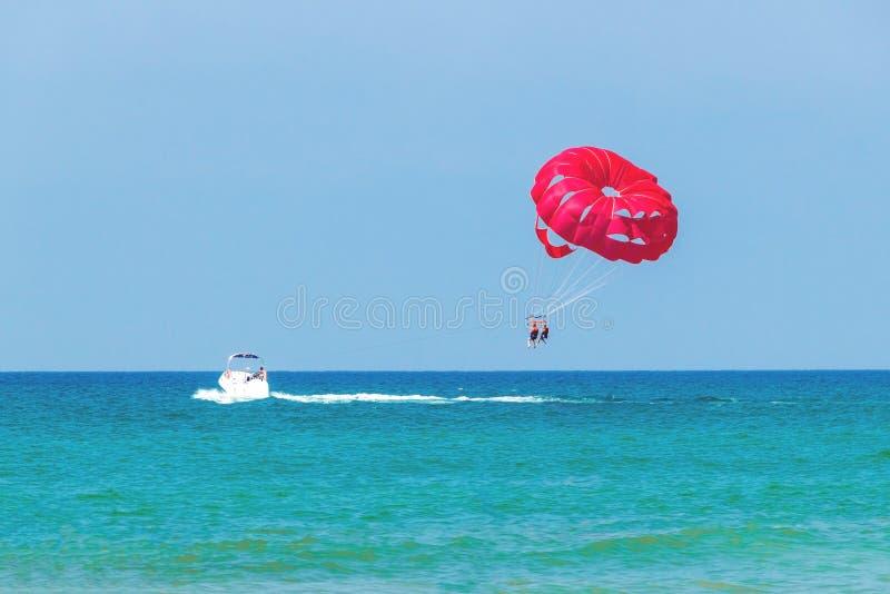Touristen haben den Spaß und springen hinter ein Boot, Parasailing mit Fallschirm ab stockbild
