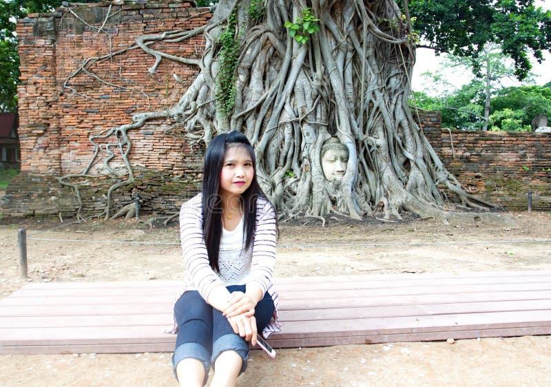 Touristen kommen, Bildern Haupt-Buddha zu nehmen, den Statue in den Feigenbaumwurzeln bei Wat Mahathat Tempel und berühmte Touris stockbilder
