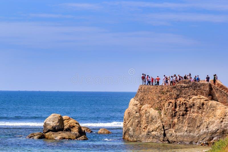 Touristen kontrollieren die Überreste der Bastion und die Festungswand des Forts auf dem Hintergrund des Meeres an einem sonnigen stockfoto