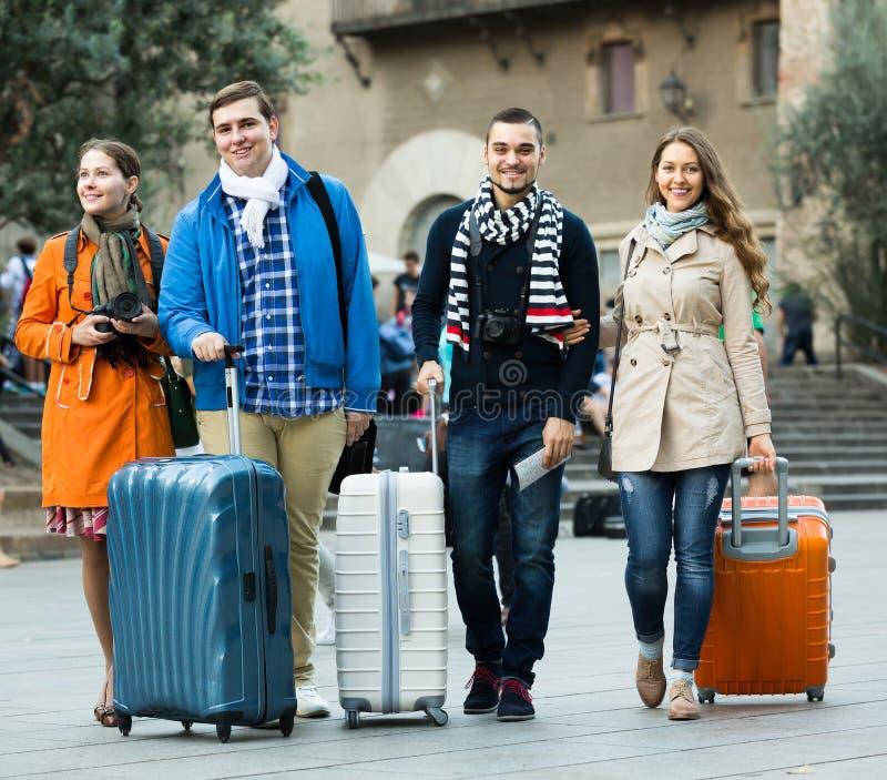 Touristen mit Gepäck gehend durch Straße lizenzfreie stockfotos