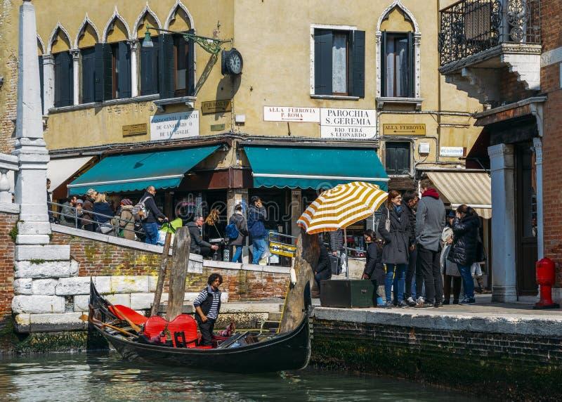 Touristen nahe bei einer Gondel auf schmalem Kanal lizenzfreie stockbilder