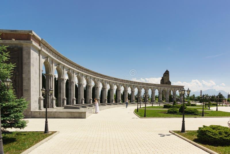Touristen nahe der Kolonnade des Denkmals des Gedächtnisses und des Ruhmes mit den Namen von Ingush 36, die Staatspreise während  lizenzfreie stockbilder