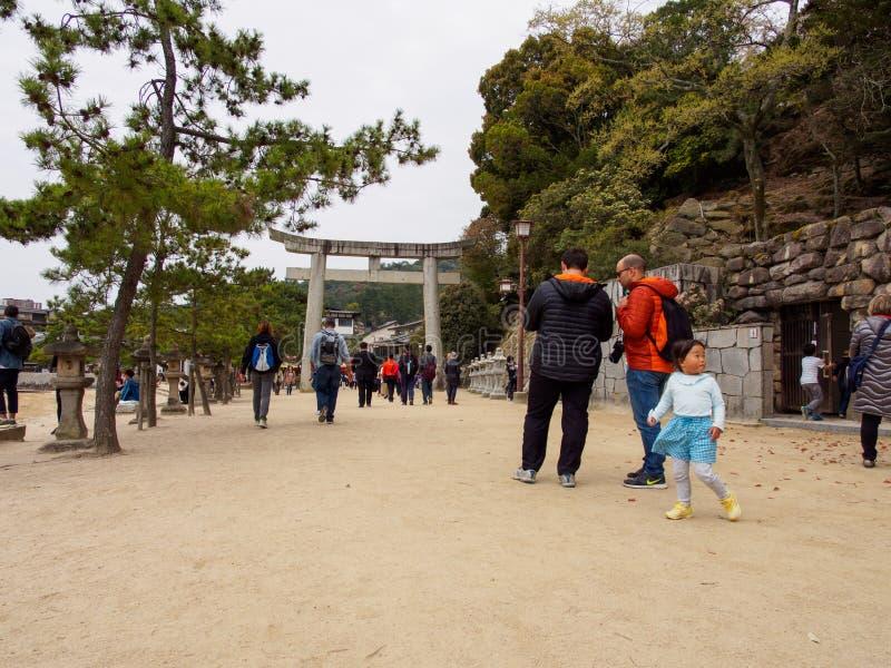 Touristen nehmen Itsukushima-Schrein durch Torii-Tor, Hiroshima, Japan heraus stockbilder