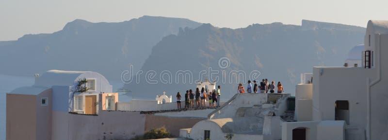 Touristen Oia Santorini auf Dach übersteigt Thirassia-Insel lizenzfreie stockfotografie