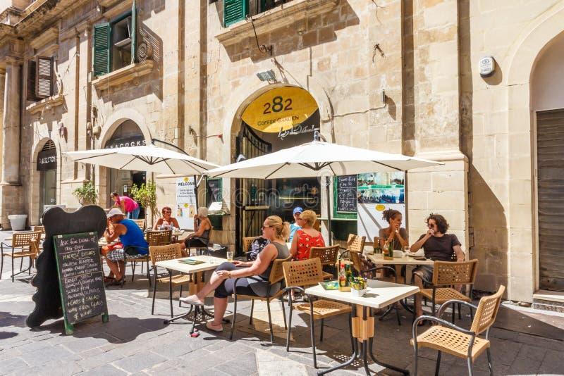 Touristen saßen außerhalb eines Cafés in einem Quadrat stockbild