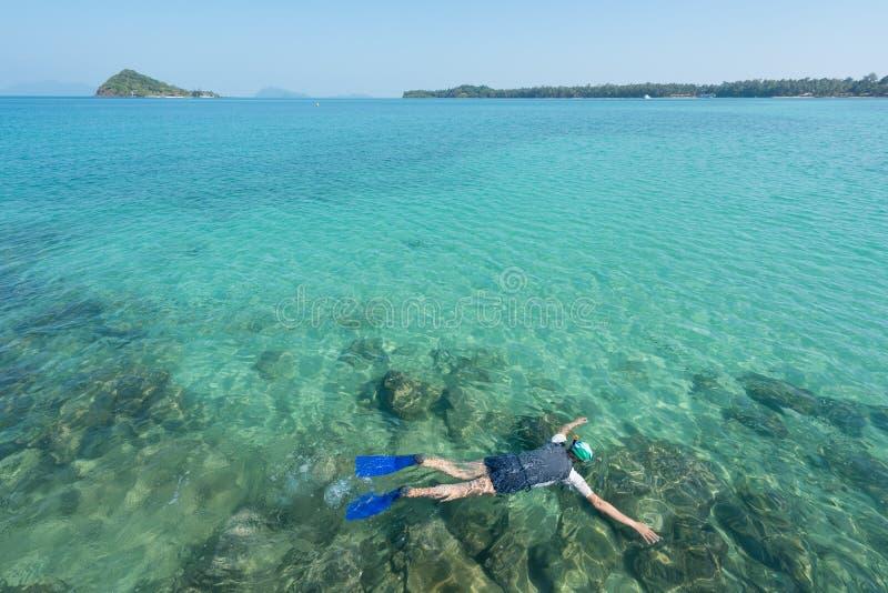 Touristen schnorcheln im Kristalltürkiswasser nahe tropischem Erholungsort stockfotos