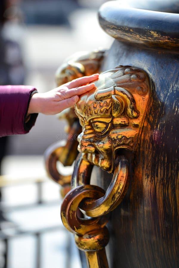 Touristen sind glücklich, die hinaufkletternde chinesische Löwe-köpfige Großmessingschüssel zu berühren stockfoto