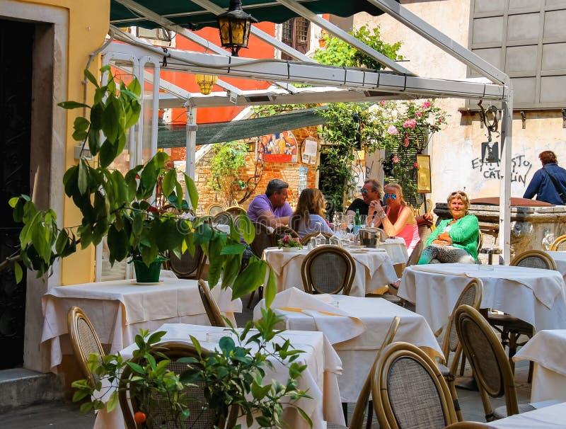 Touristen stehen an den Tischen in einem Café im Freien in Venedig, Italien still stockfotos