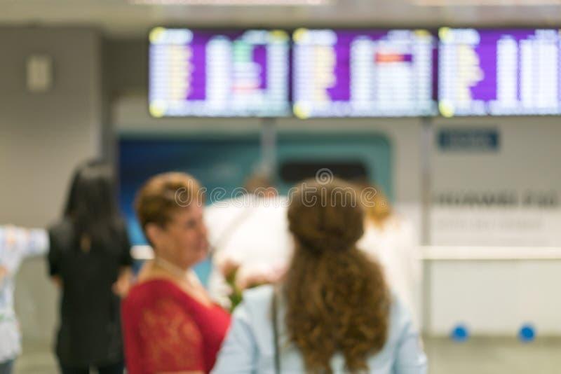 Touristen stehen vor einem Informationen Brett innerhalb des Flughafens Verwischen Sie Bild von den Leuten, die vor Flughafen war lizenzfreies stockbild