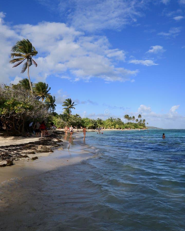 Touristen und Einheimische, die einen Strand in tropischem Paradise teilen lizenzfreie stockbilder