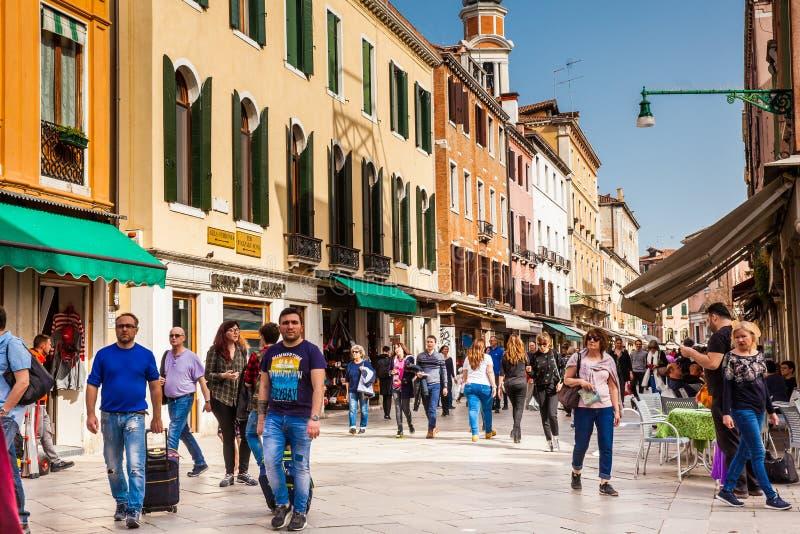 Touristen und Einheimische, die um die schönen Straßen von Venedig an einem sonnigen Vorfrühlingstag gehen stockbilder