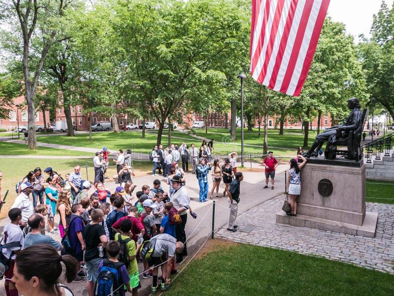 Touristen und Reisegruppe durch John Harvard-Statue in Harvard-Yard stockbild