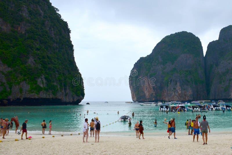 Touristen und touristische Boote auf dem berühmten Strand in Maya Bay auf einer der Inseln von Phi Phi, Thailand stockbilder
