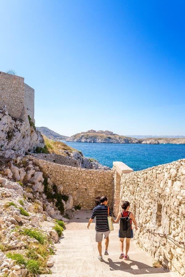 Touristen, welche die Festung in der Insel von wenn besichtigen Im Hintergrund die Insel von Ratonneau von Friulian-Archipel, Fra stockfoto