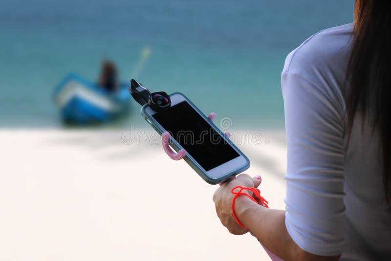 Touristenmädchen halten das intelligente Telefon mit Griff und Fall lizenzfreies stockbild