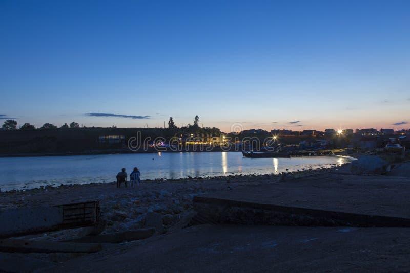 Touristes admirant le coucher du soleil et la petite baie images stock