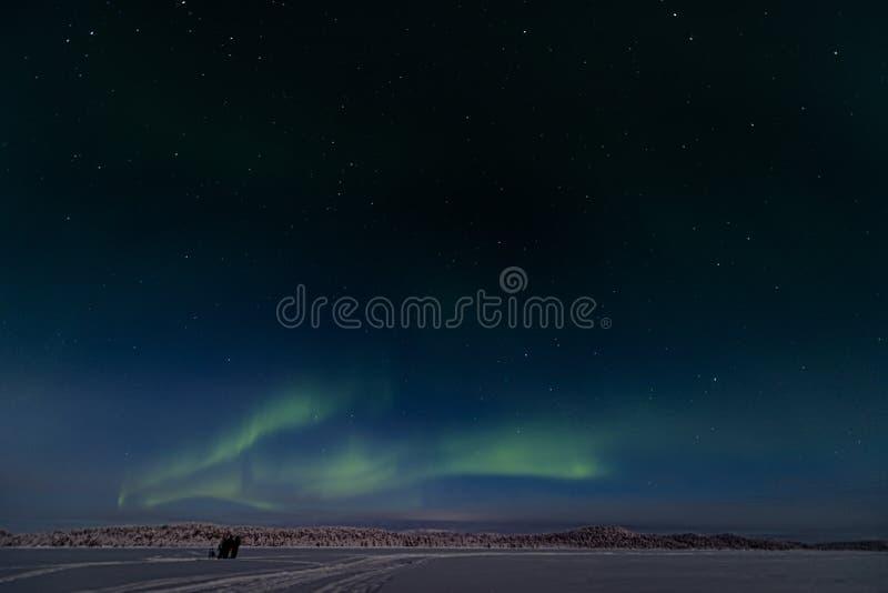 3 touristes adoptent des photgraphs et la position les lumières du nord à travers le lac congelé et vers les forêts photos stock