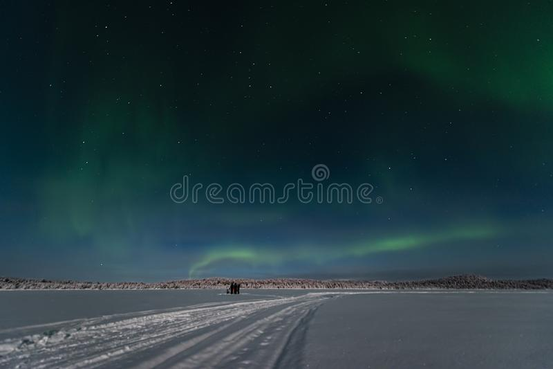 3 touristes adoptent des photgraphs et la position les lumières du nord à travers le lac congelé et vers les forêts photos libres de droits
