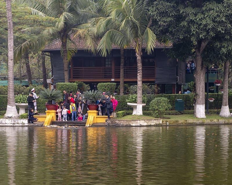Touristes alimentant la carpe avec la Chambre d'échasse de Ho Chi Minh à l'arrière-plan, Hanoï, Vietnam photo libre de droits