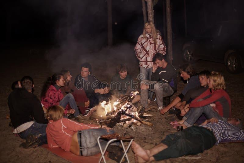 Touristes autour du feu de camp la nuit photographie stock libre de droits