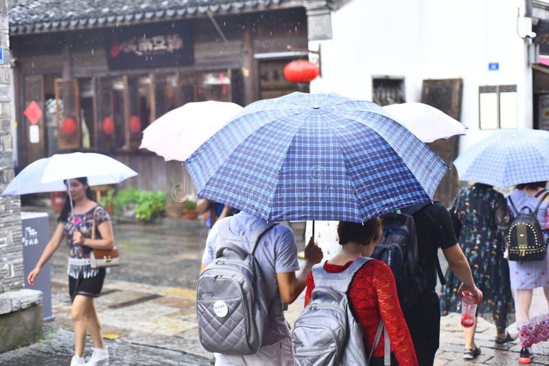 Touristes avec des parapluies dans la tache scénique pluvieuse image stock