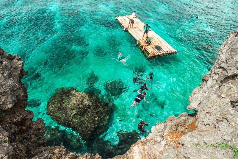 Touristes chinois de groupe naviguant au schnorchel en mer de turquoise au sujet de la côte rocheuse de l'île de Crystal Cove prè image stock