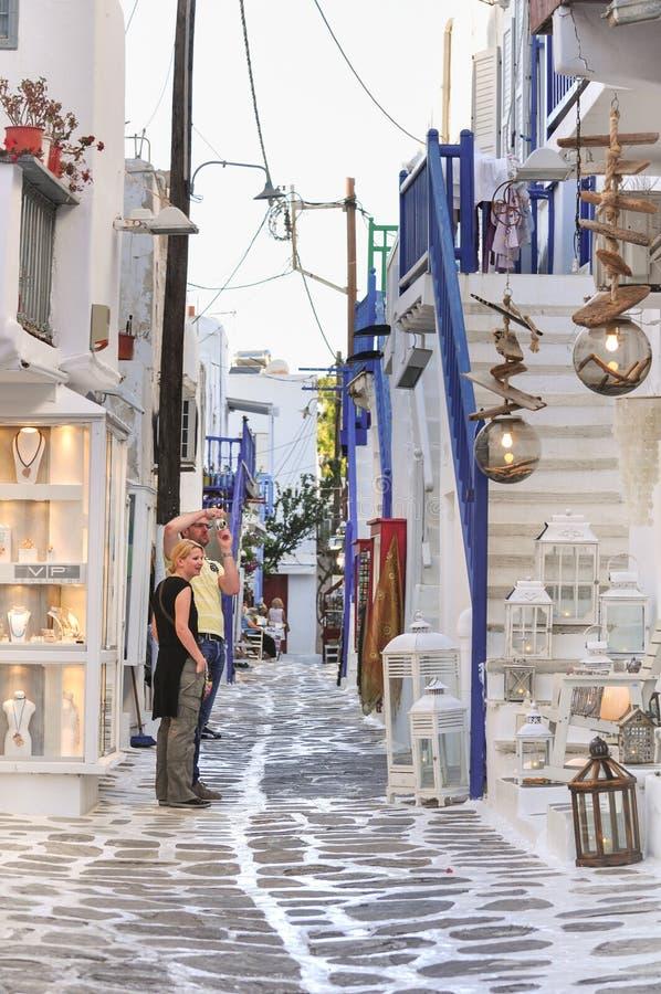 Touristes dans la petite allée, ville de Mykonos, Grèce image stock