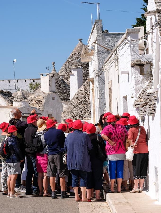 Touristes dans la ville de Puglian d'Alberobello, regardant et photographiant les maisons de pierres sèches traditionnelles de tr images libres de droits