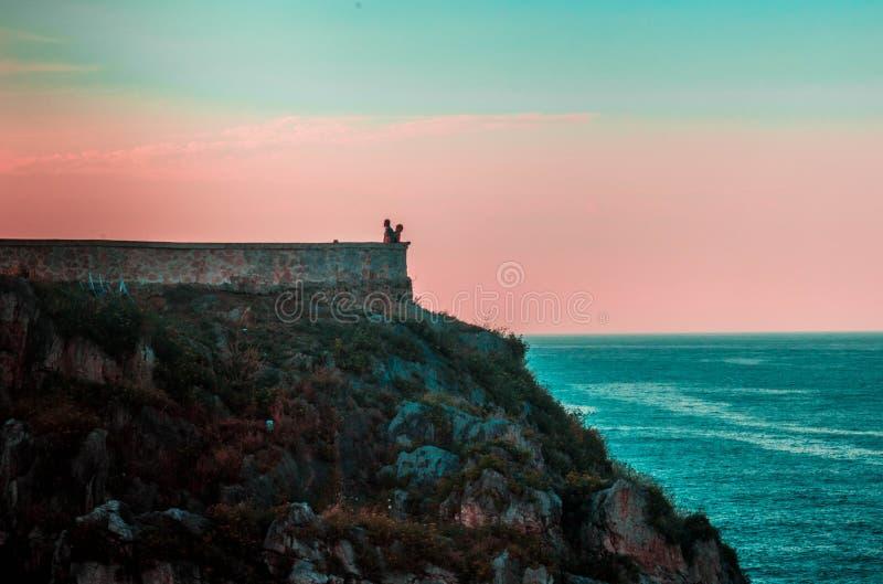 Touristes dans le dessus d'une falaise admirant la vue de l'horizon et de l'océan image libre de droits