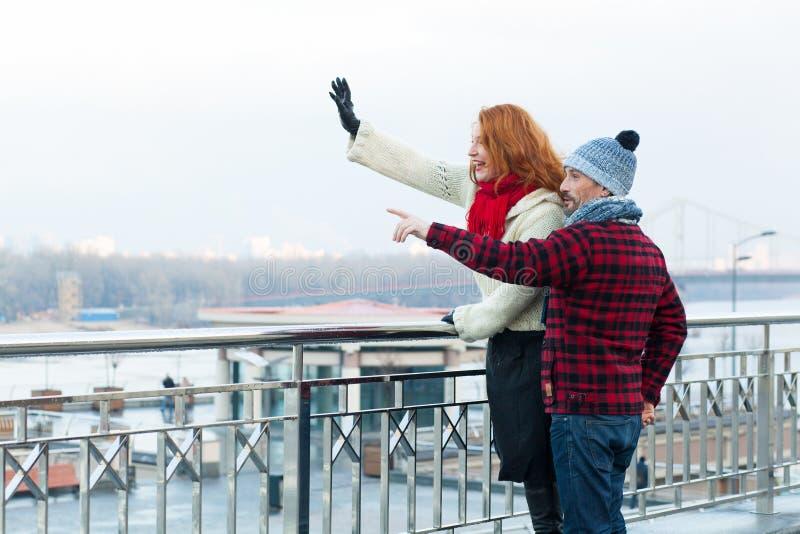 Touristes de couples regardant la ville visitant le pays Couples heureux indiquant loin à la main et la position près de la barri image stock