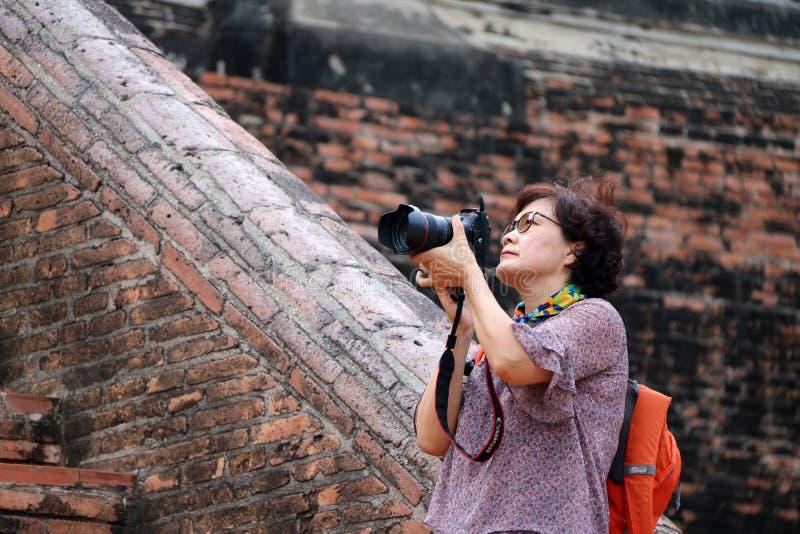 Touristes de femmes prenant les photos et le fond brique antique au temple de Yai Chaimongkol, Thaïlande image stock
