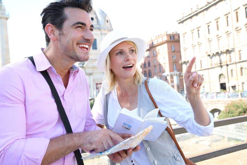 Touristes employant la carte et guide pour visiter Rome images libres de droits