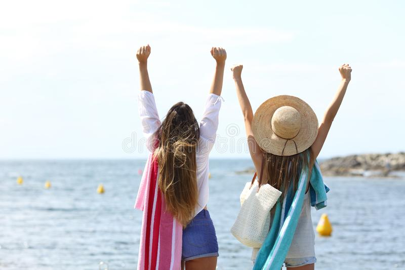 Touristes enthousiastes soulevant des bras célébrant des vacances sur la plage photo stock