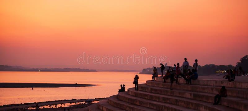 Touristes et Laotien détendant sur le pilier par le Mekong pendant le coucher du soleil serein Vientiane, Laos photos libres de droits