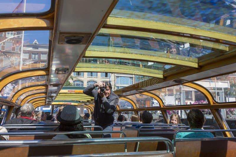 Touristes et photographe à l'intérieur de l'embarcation de plaisance à Amsterdam photo libre de droits