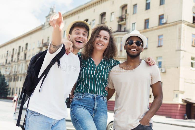 Touristes heureux étreignant et marchant dans la rue photo stock