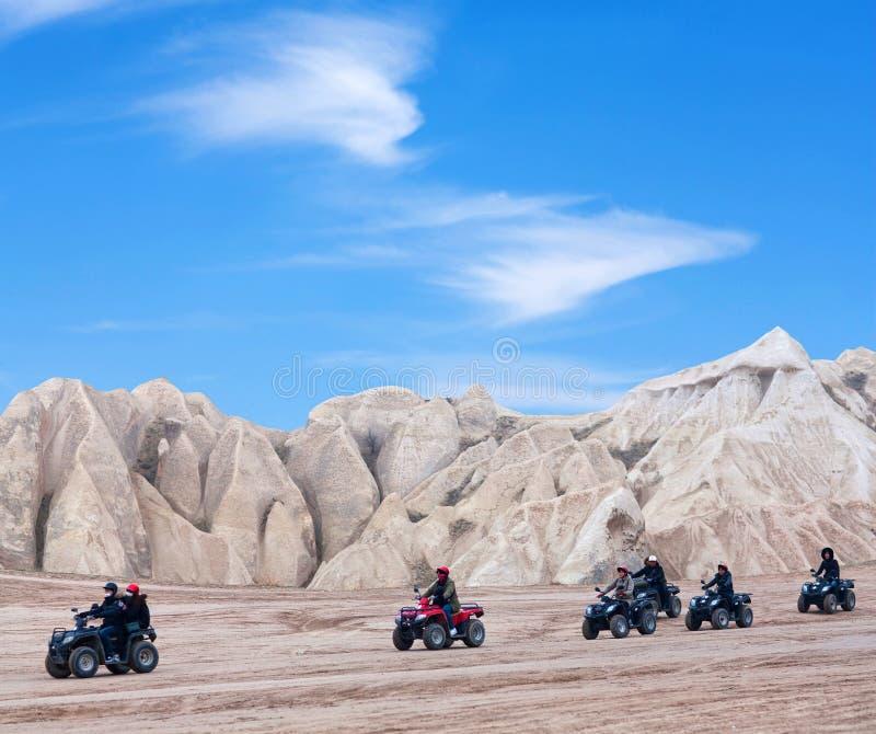 Touristes heureux appr?ciant un tour de v?lo de quadruple dans Cappadocia, Turquie photos libres de droits