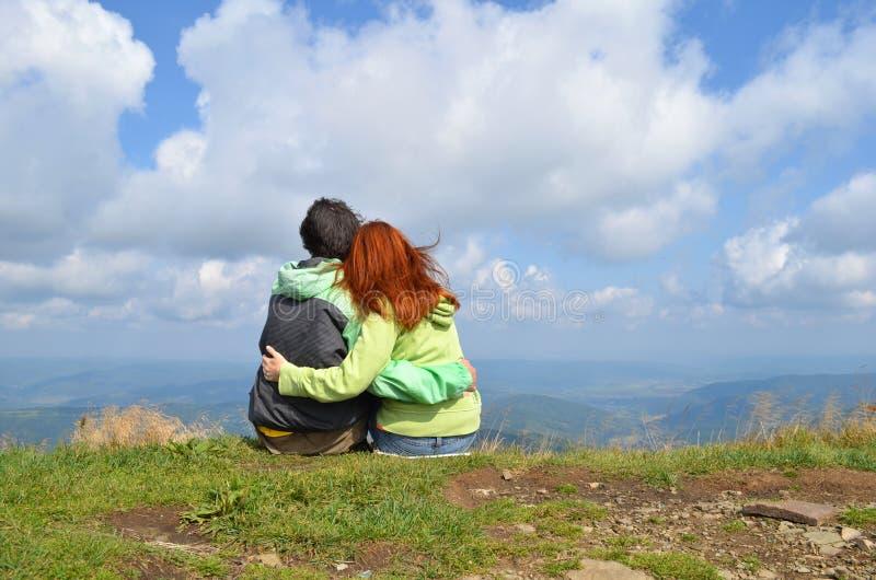 Touristes heureux d'homme blanc et de femme dans des vêtements verts reposant étreindre au bord du dessus de la montagne photo stock